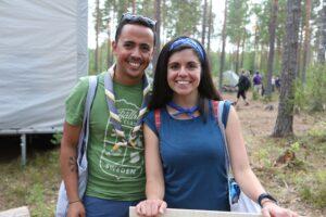 Kaksi hymyilevää henkilöä poseeraa kameralle metsässä.